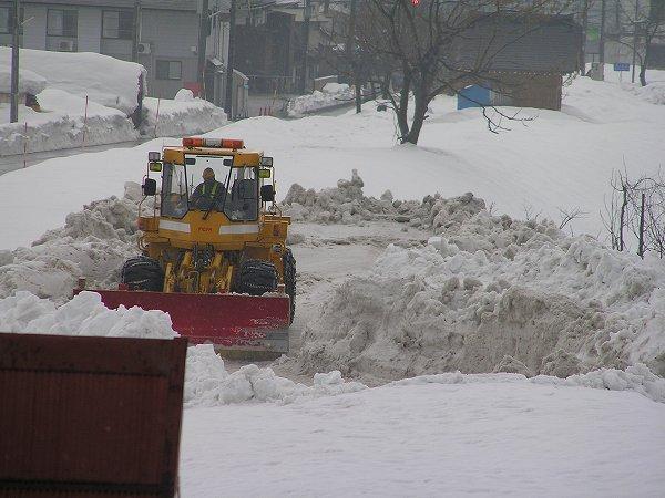 水無川の土手の雪捨て場ではブルドーザーが動いています