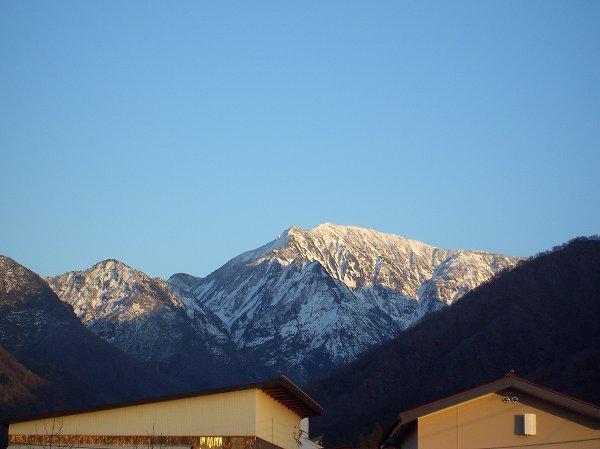 雪化粧した駒ケ岳が夕日に照らされて輝いています