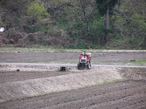 田んぼの脇にトラクターがスタンバイしています